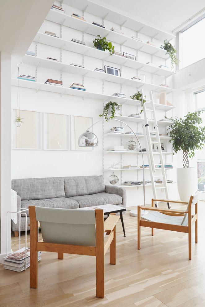 Imagen de salón escandinavo, sin chimenea y televisor, con paredes blancas y suelo de madera clara