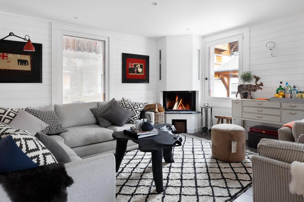 Inspiration pour un salon nordique de taille moyenne et ouvert avec un mur blanc, un sol en bois brun, une cheminée d'angle et aucun téléviseur.