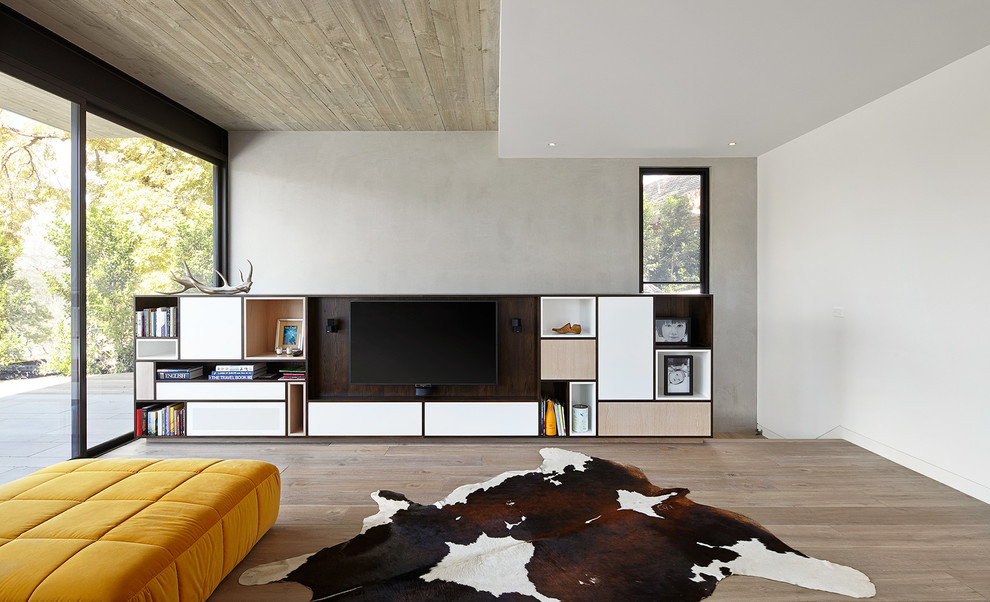 Living room - scandinavian open concept light wood floor living room idea in Melbourne with white walls and a media wall
