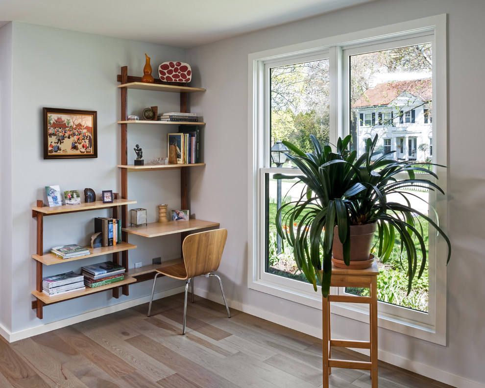 Example of a mid-sized danish open concept light wood floor living room library design in Milwaukee with white walls