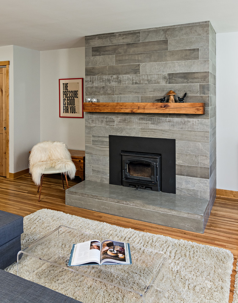 Living room - mid-sized scandinavian open concept medium tone wood floor living room idea in Minneapolis with white walls, a wood stove, a tile fireplace and a tv stand