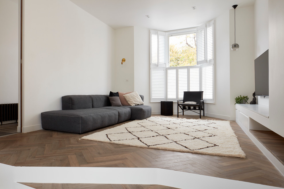 Inspiration for a large contemporary open concept medium tone wood floor living room remodel in London with white walls and a wall-mounted tv