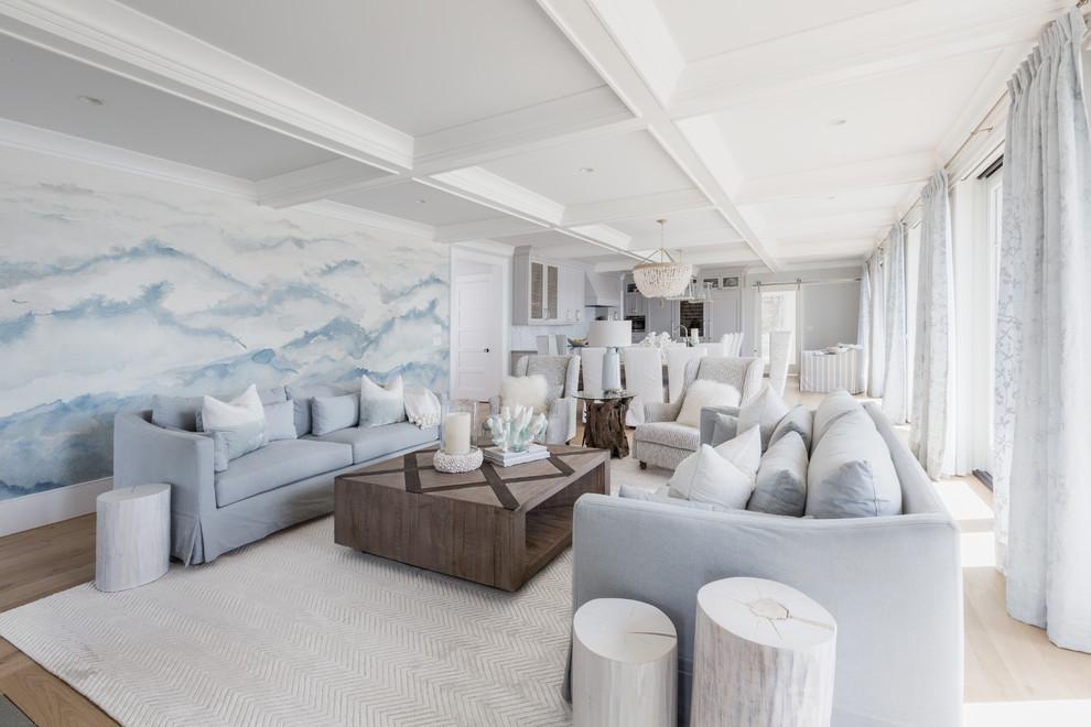 Immagine di un soggiorno stile marino aperto con pareti blu, parquet chiaro e pavimento beige