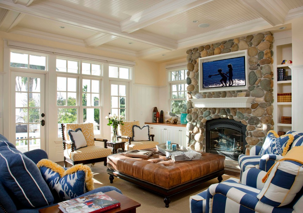 Example of a classic living room design in San Diego with beige walls, a standard fireplace, a stone fireplace and a wall-mounted tv