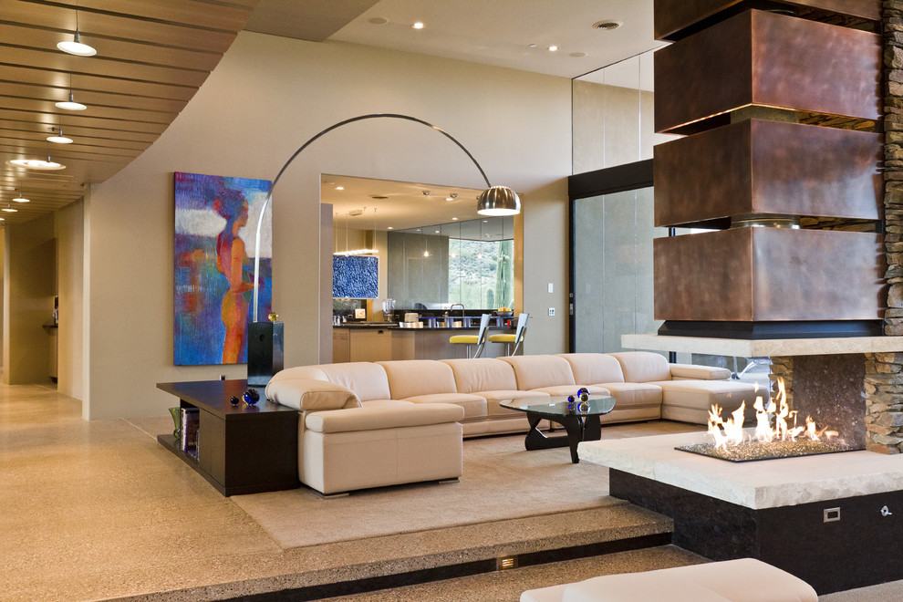 Southwest living room photo in Phoenix with beige walls and a two-sided fireplace