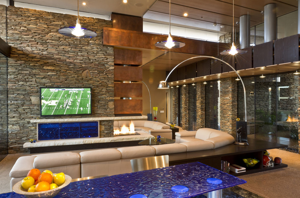 Huge southwest open concept concrete floor and beige floor living room photo in Phoenix with a wall-mounted tv, a two-sided fireplace and a stone fireplace