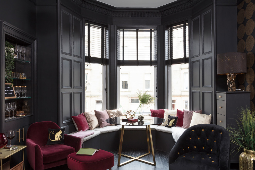 Small trendy enclosed dark wood floor and black floor living room photo in Other with black walls