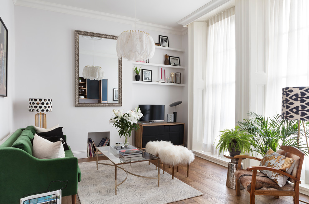Danish medium tone wood floor and brown floor living room photo with white walls and a tv stand