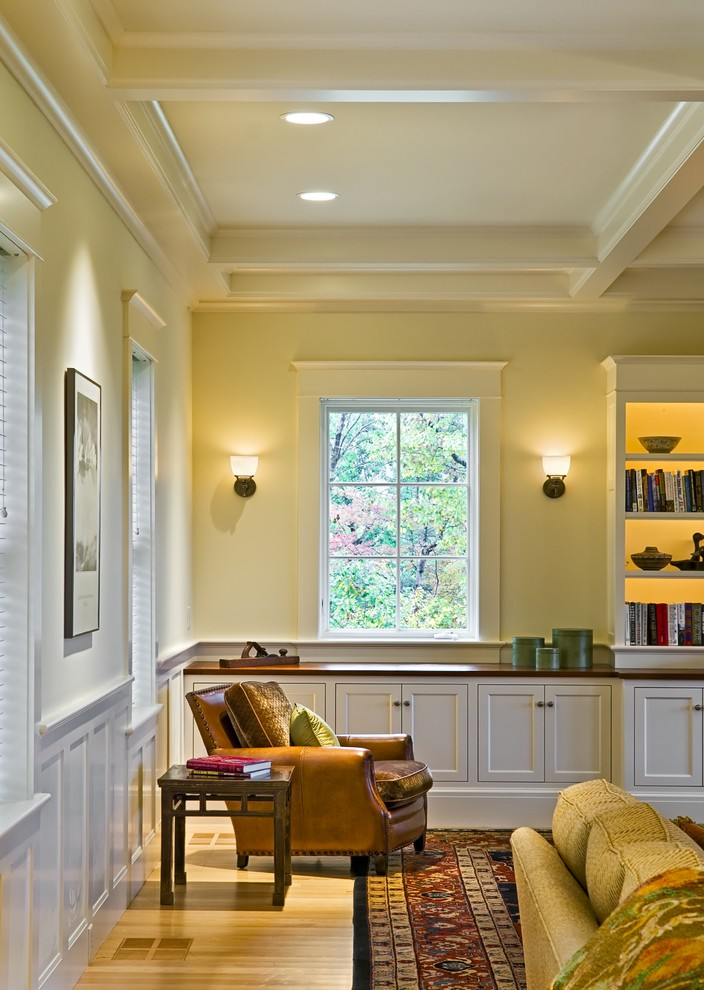 Example of an ornate living room library design in Burlington with yellow walls