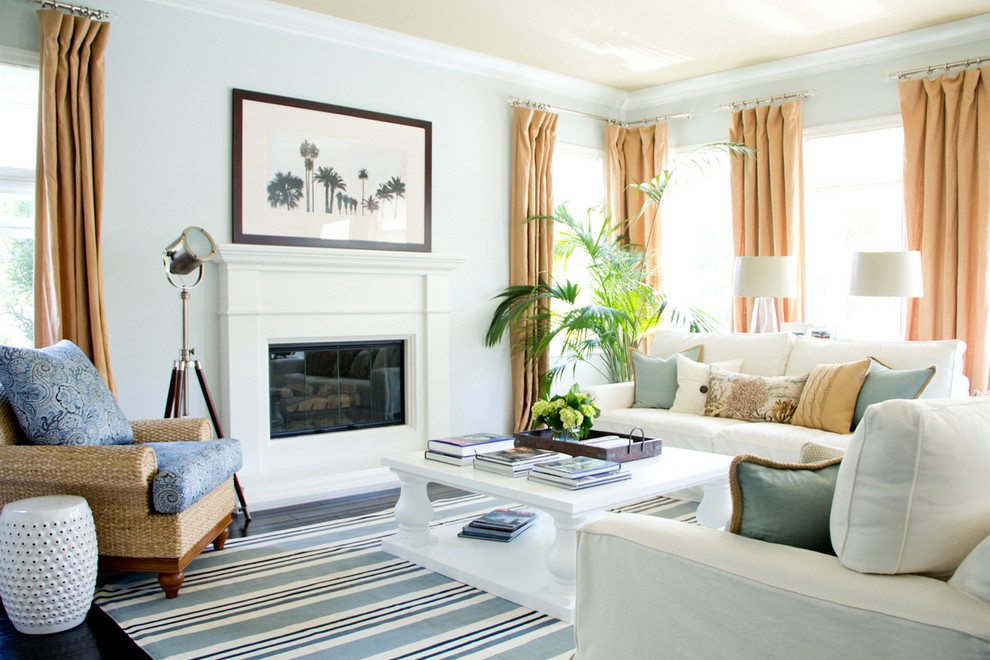 Example of a mid-sized island style living room design in Los Angeles with gray walls, a standard fireplace, a plaster fireplace and no tv