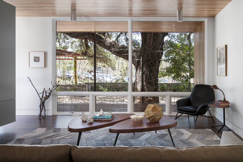 Example of a large minimalist formal and open concept medium tone wood floor, brown floor and wood ceiling living room design in Austin with white walls and a media wall