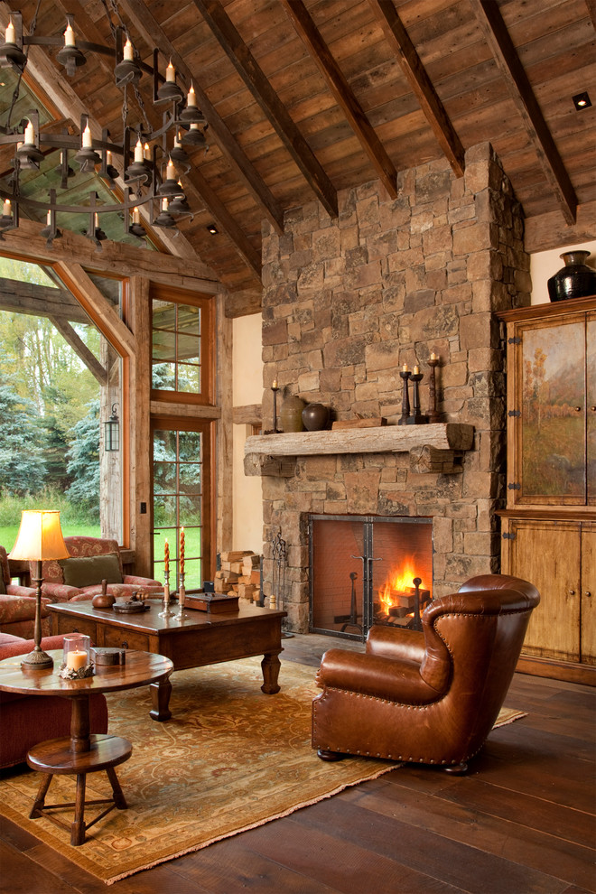 Mountain style medium tone wood floor living room photo in Other with a stone fireplace