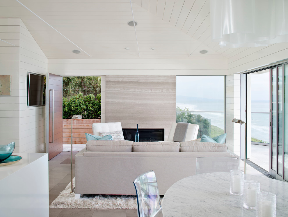 Example of a mid-sized beach style open concept living room design in San Diego with white walls and a wall-mounted tv