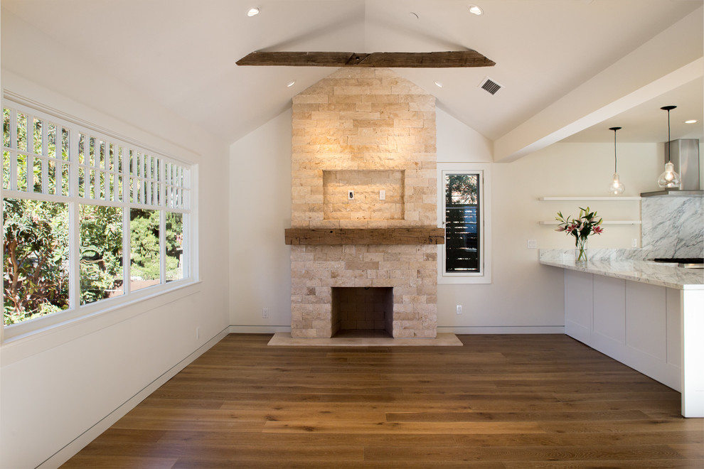 Minimalist open concept medium tone wood floor living room photo in San Francisco with white walls, a standard fireplace and a stone fireplace