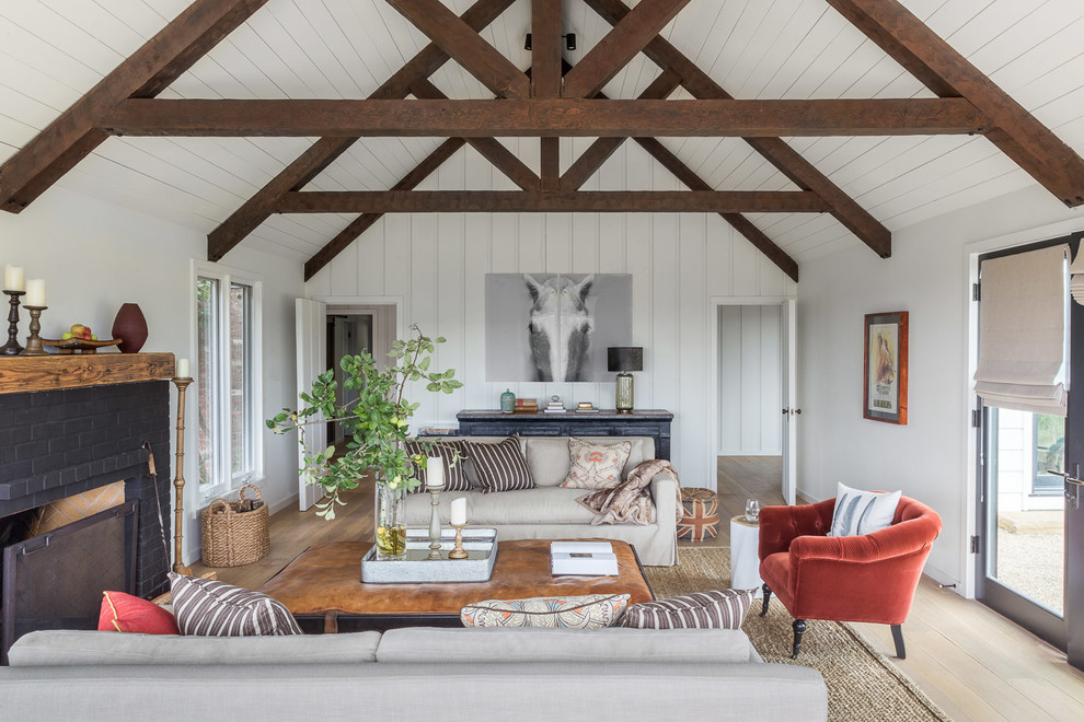 Example of a farmhouse formal light wood floor and beige floor living room design in San Francisco with white walls, a standard fireplace and a brick fireplace