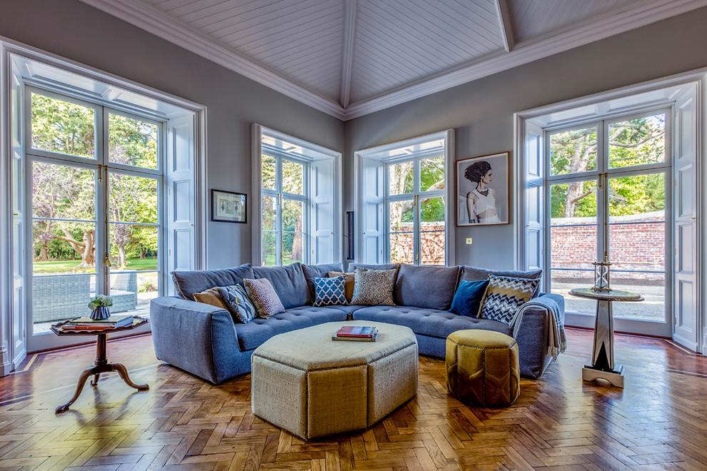 Ejemplo de salón para visitas tradicional renovado, sin chimenea y televisor, con paredes grises y suelo de madera en tonos medios