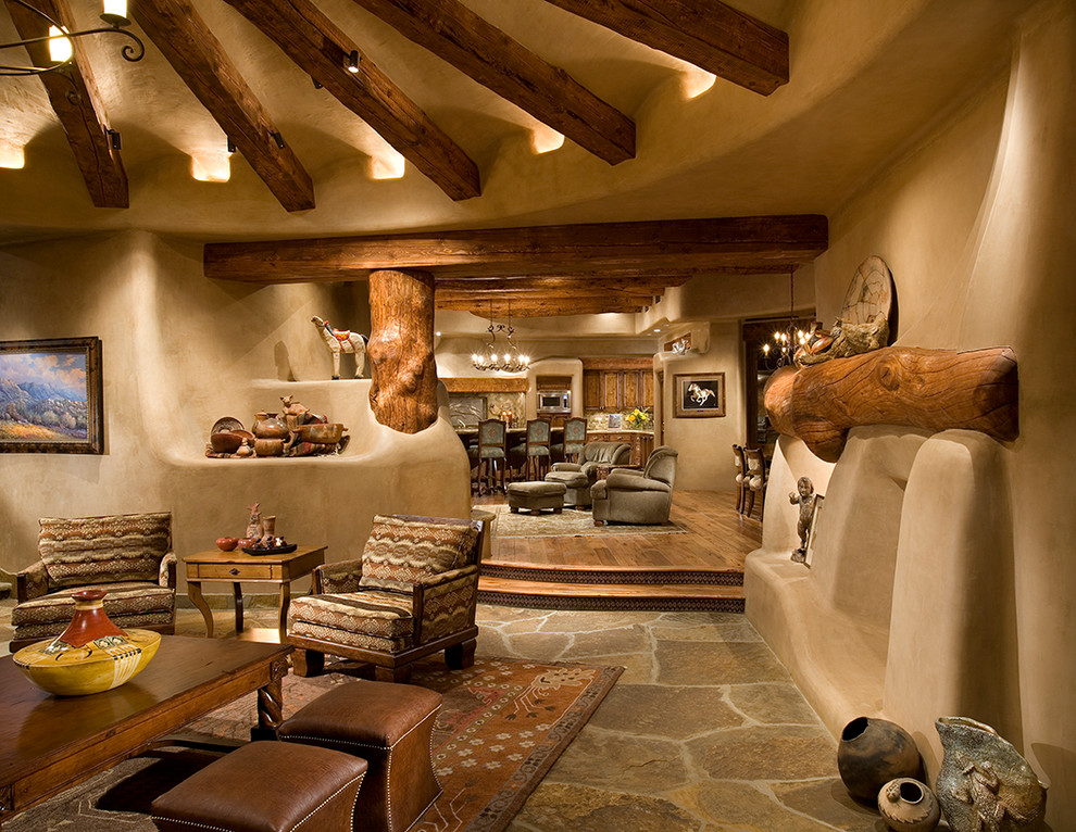 Example of a southwest living room design in Phoenix with beige walls, a standard fireplace and a plaster fireplace