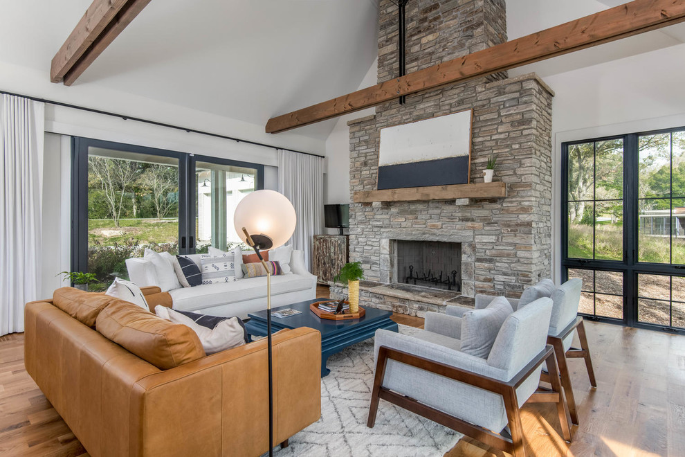 Example of a country open concept medium tone wood floor and brown floor living room design in Other with white walls, a standard fireplace and a stone fireplace