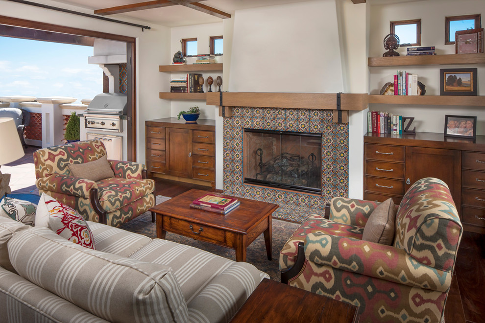 Example of a tuscan living room design in Los Angeles with a standard fireplace and a tile fireplace
