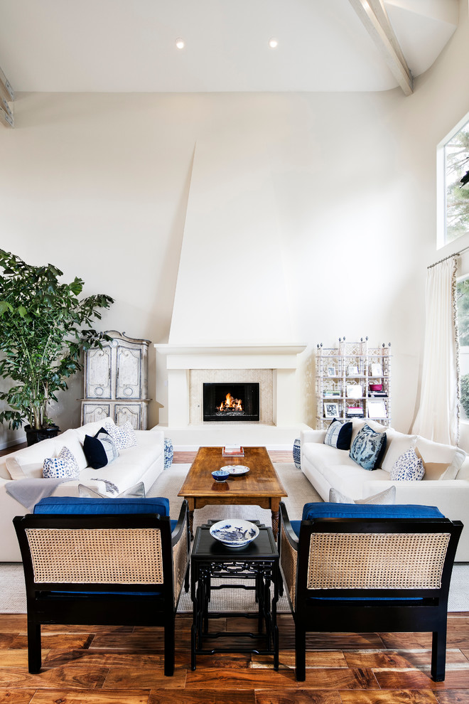 Large beach style formal and open concept medium tone wood floor living room photo in Los Angeles with white walls, a standard fireplace, a stone fireplace and no tv