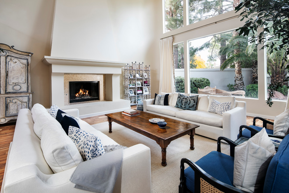 Example of a large beach style formal and open concept medium tone wood floor living room design in Los Angeles with white walls, a standard fireplace, a stone fireplace and no tv