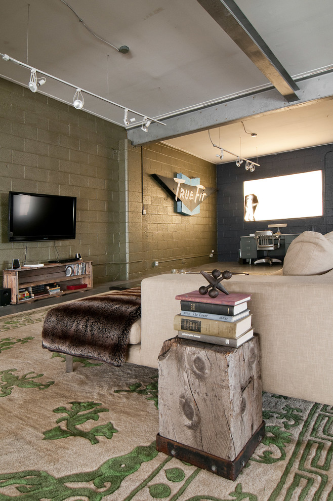 Living room - industrial open concept living room idea in Salt Lake City with a wall-mounted tv