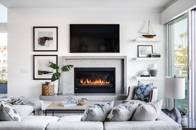 Example of a mid-sized coastal open concept medium tone wood floor and brown floor living room design in Los Angeles with white walls, a standard fireplace, a wall-mounted tv and a stone fireplace