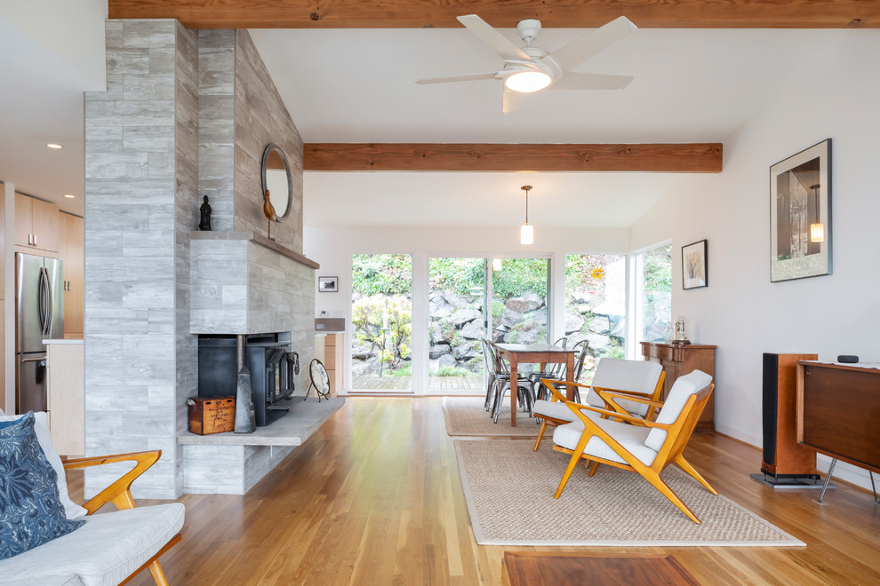 Trendy open concept medium tone wood floor and brown floor living room photo in Seattle with white walls and a ribbon fireplace