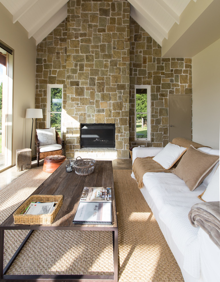Example of a mid-sized country open concept concrete floor living room design in Wollongong with beige walls, a standard fireplace, a stone fireplace and no tv