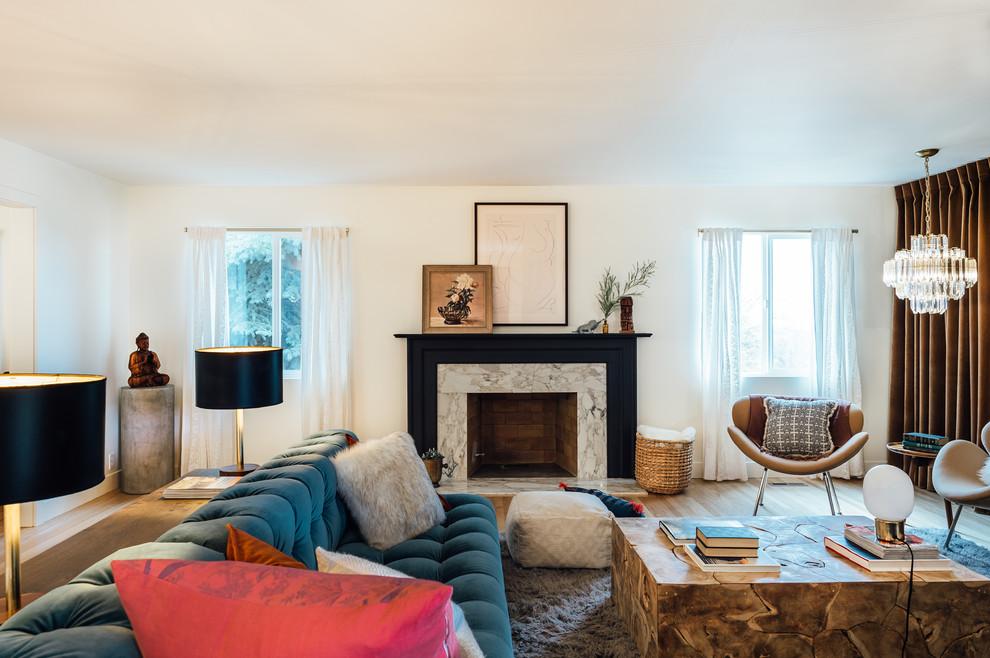 Foto di un soggiorno bohémian di medie dimensioni e aperto con pareti bianche, pavimento in legno massello medio, camino classico e cornice del camino in pietra