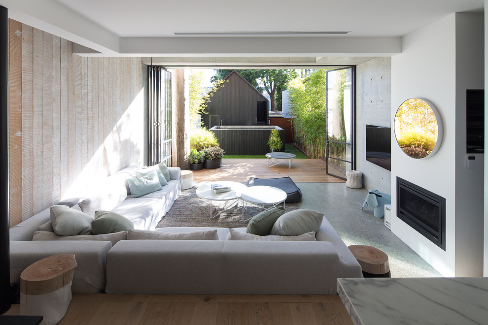 Inspiration for a contemporary enclosed concrete floor and gray floor living room remodel in Sydney with a standard fireplace, a plaster fireplace and a wall-mounted tv