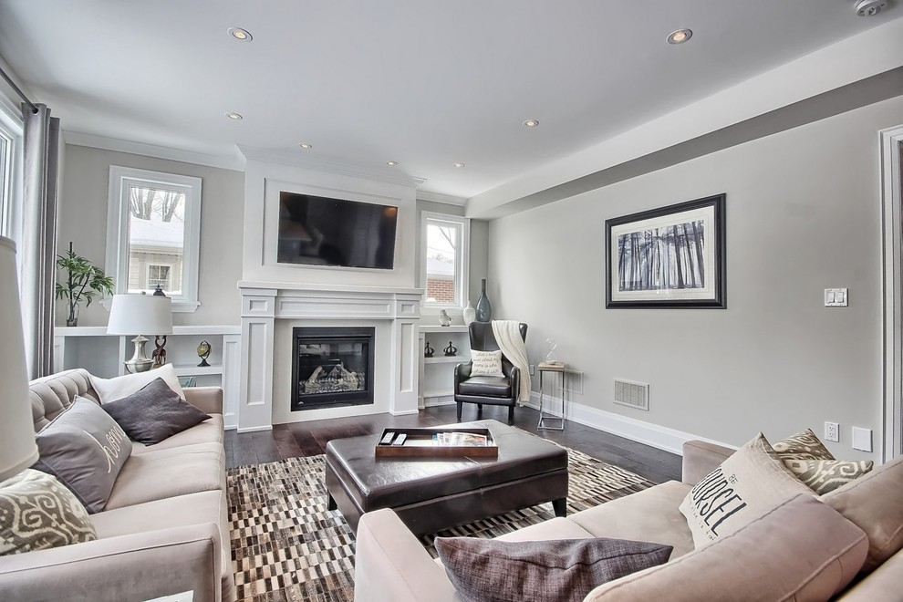 Mid-sized transitional open concept dark wood floor living room photo in Toronto with a standard fireplace, a wood fireplace surround, a wall-mounted tv and gray walls