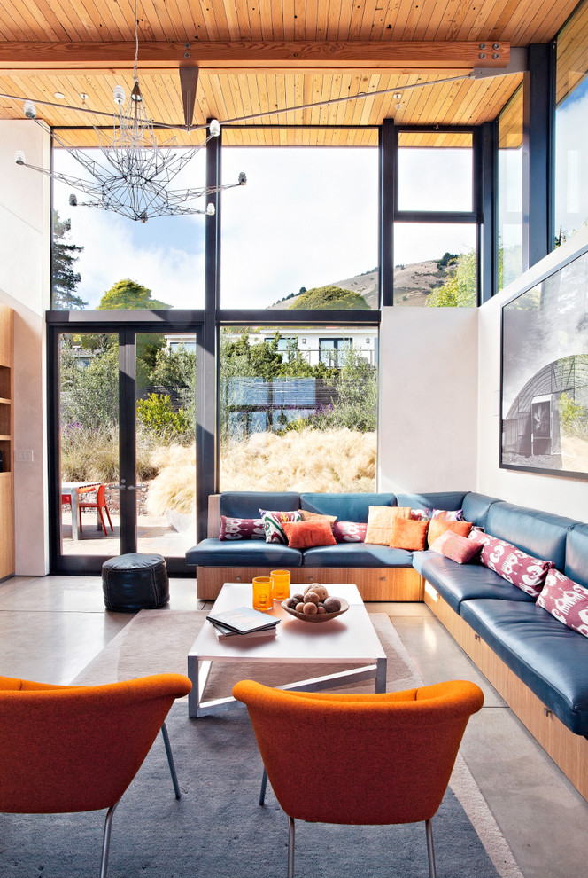 Living room - large coastal concrete floor living room idea in San Francisco with white walls and a wall-mounted tv