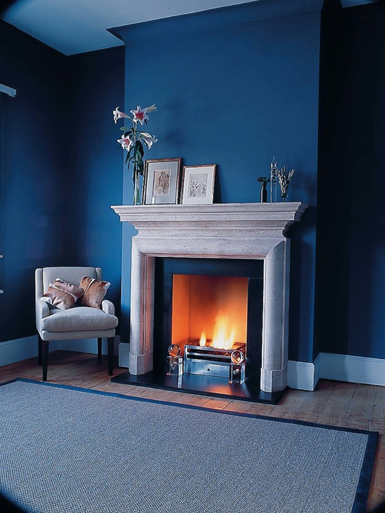Stirling - A striking design of elegant simplicity with a strong architectural form, the Stirling incorporates a corniced mantel shelf and bolection moulding in the frieze and jambs. Shown in Italian Bianco Avorio limestone with Glass Globe fire dogs, Universal fire basket for dogs and black slate hearth and slips.