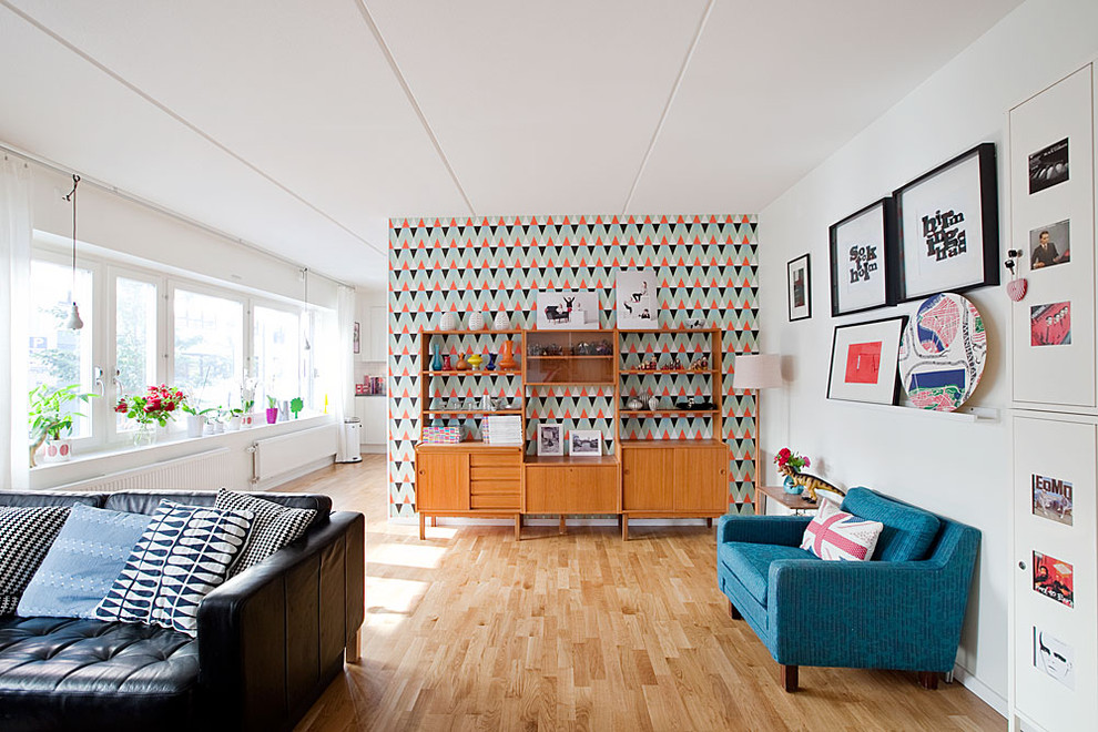 Example of a mid-sized mid-century modern open concept light wood floor living room design in Stockholm with white walls, no fireplace and no tv