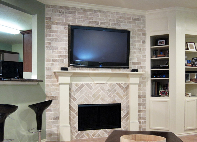 Dual pattern brick fireplace with built-in wood mantle and recessed television mount with surround sound speakers and concealed wiring.