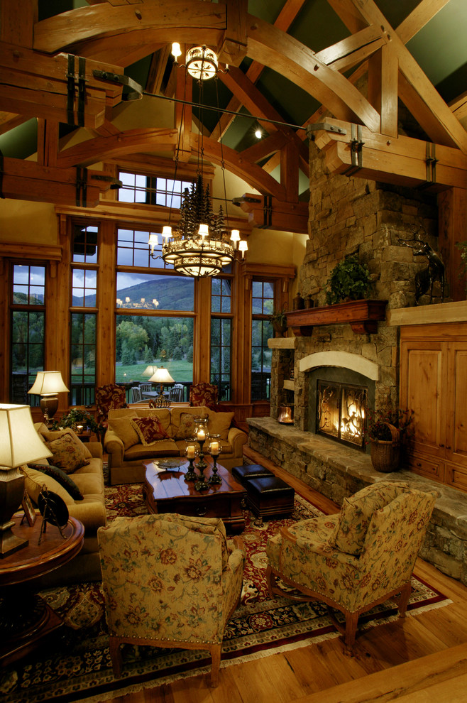 Example of a mountain style medium tone wood floor living room design in Denver with a standard fireplace and no tv