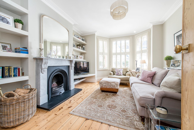 Mid-sized transitional enclosed medium tone wood floor living room photo in London with beige walls, a standard fireplace, a tv stand and a stone fireplace
