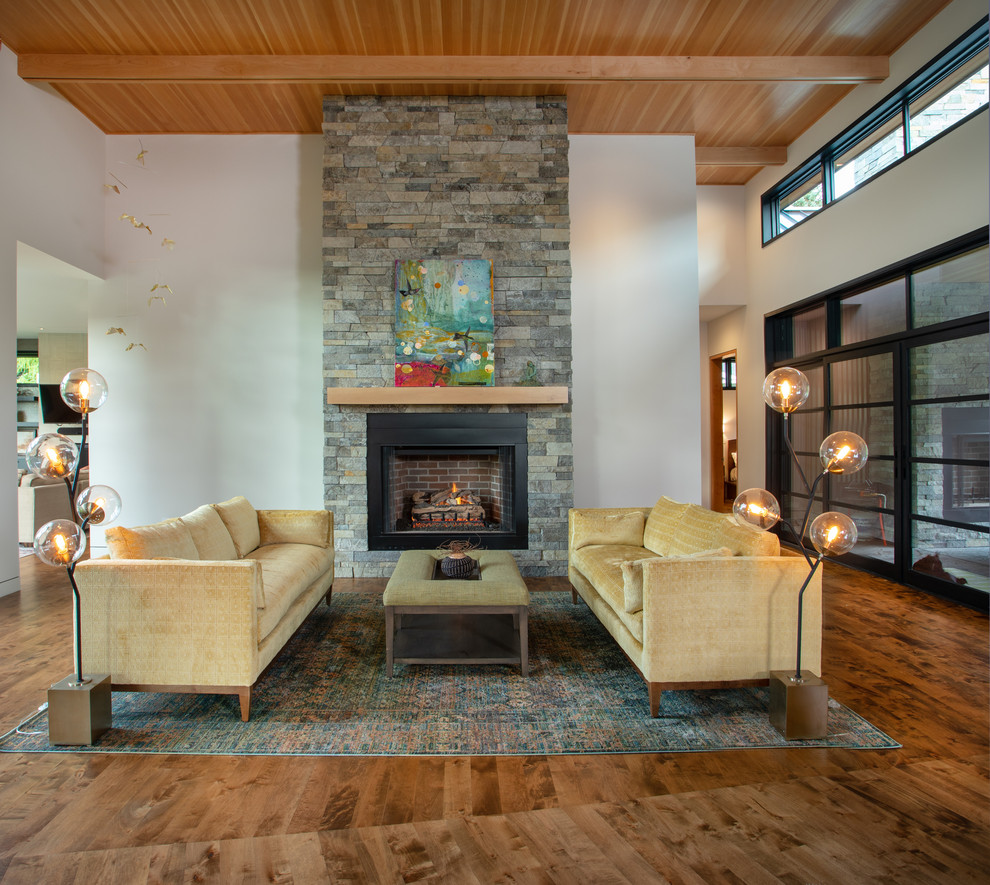 Large trendy open concept medium tone wood floor and brown floor living room photo in Other with white walls, a standard fireplace, a stone fireplace and no tv