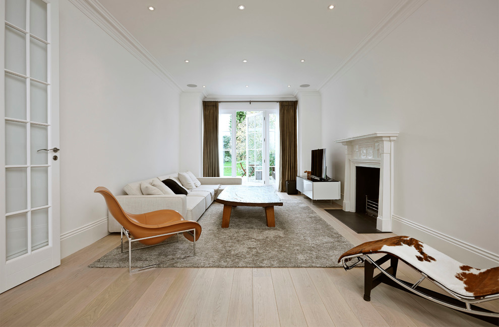Living room - large scandinavian formal and enclosed light wood floor living room idea in London with white walls, a standard fireplace and a tv stand