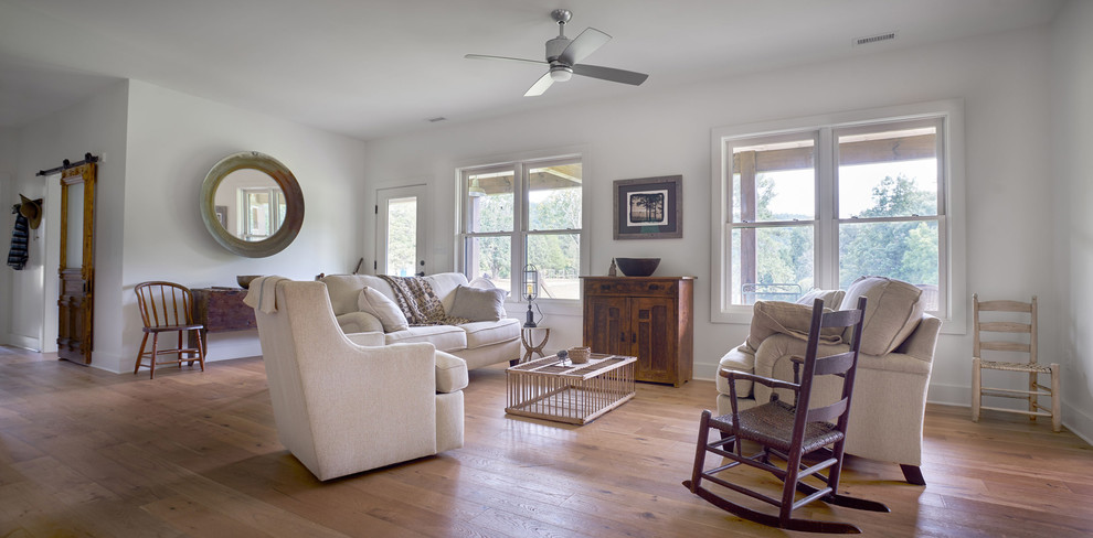 Example of a mid-sized cottage open concept light wood floor living room design in Other