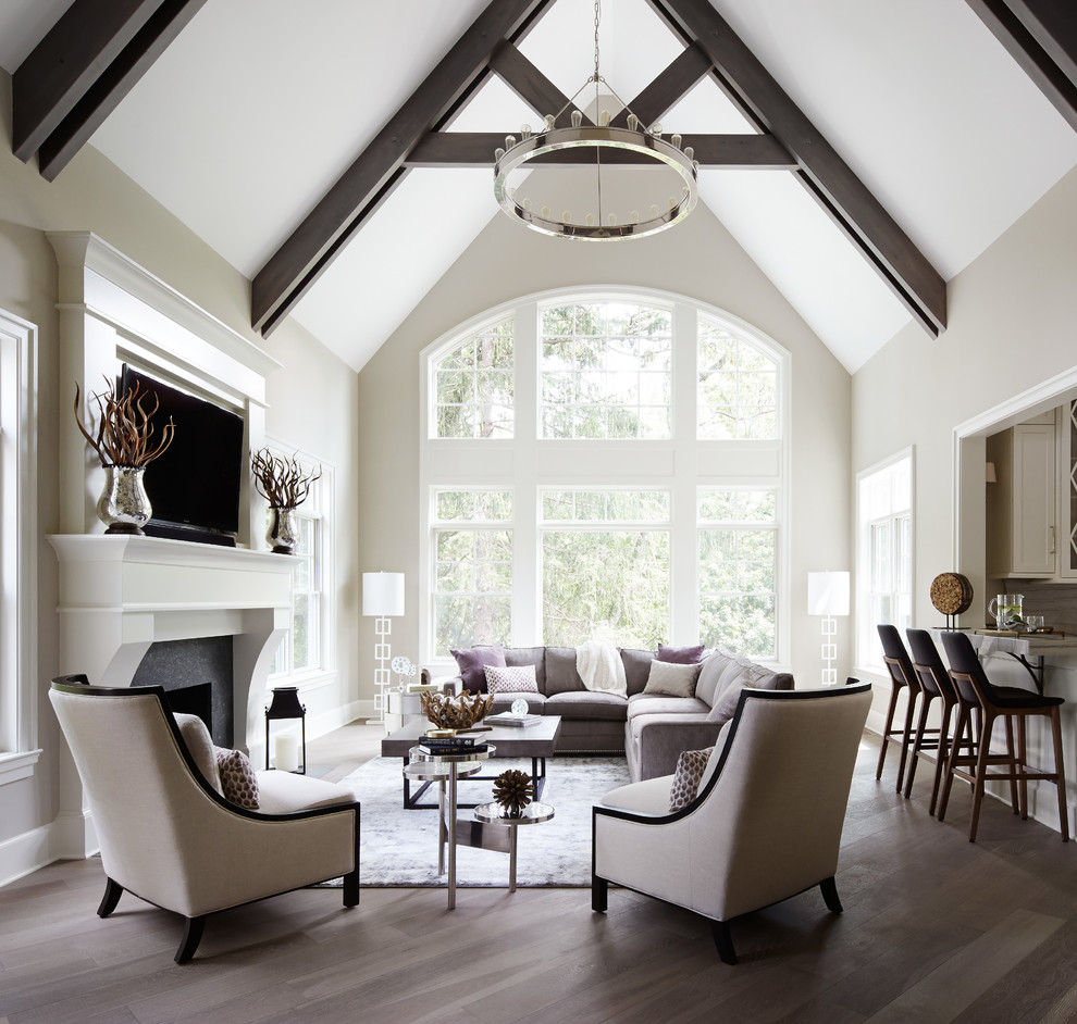 Example of a large transitional open concept medium tone wood floor living room design in Chicago with a bar, a standard fireplace, a wall-mounted tv, beige walls and a stone fireplace