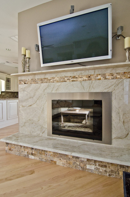 Custom Taj Mahal Quartzite fireplace surround with rough onyx tile set halfway into the solid quartzite slab.   See the rest of this kitchen by following this