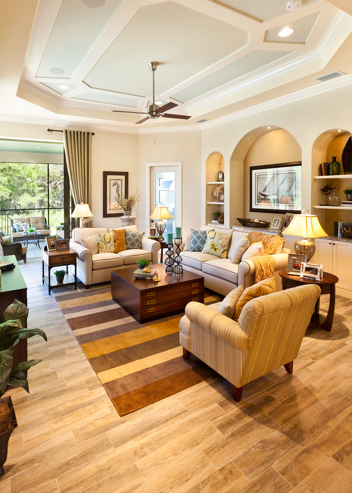 Inspiration for a large timeless open concept porcelain tile living room remodel in Tampa with beige walls, no fireplace and a wall-mounted tv