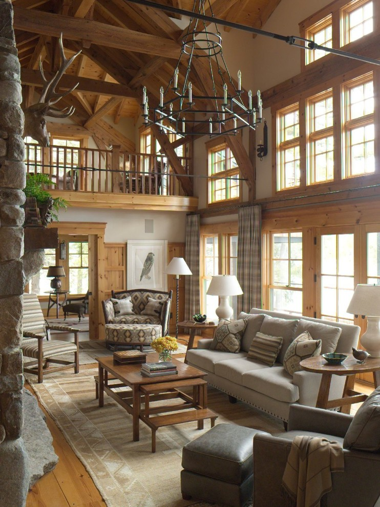 Imagen de salón abierto, rural, con paredes blancas, suelo de madera en tonos medios, todas las chimeneas, marco de chimenea de piedra y suelo marrón