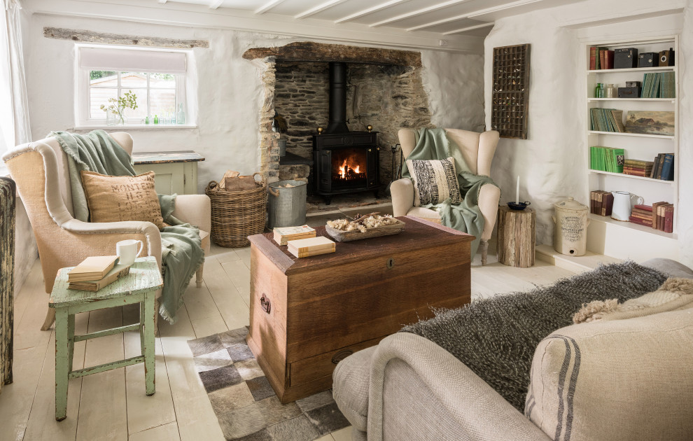 Mid-sized cottage chic painted wood floor and white floor living room photo in Cornwall with white walls, a standard fireplace and a stone fireplace
