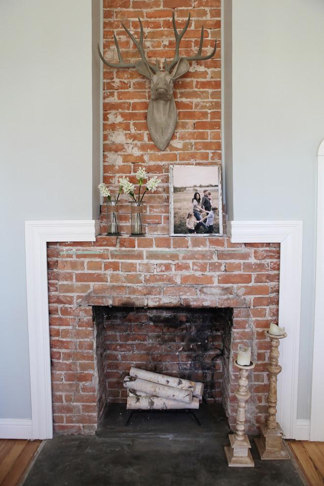 Small cottage enclosed medium tone wood floor living room photo in Austin with gray walls, a standard fireplace, a brick fireplace and no tv