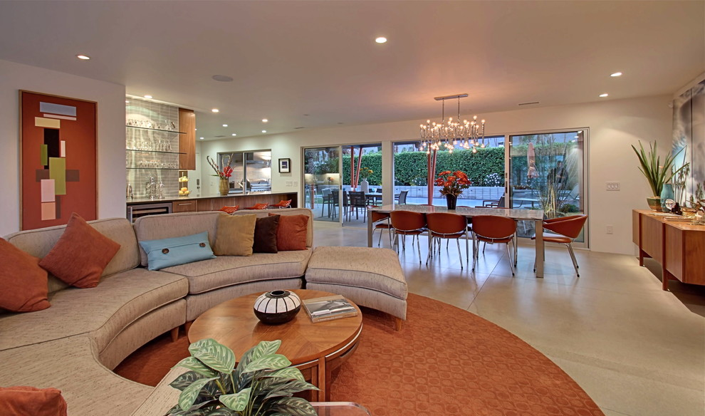 Example of a large mid-century modern open concept concrete floor living room design in Los Angeles with white walls