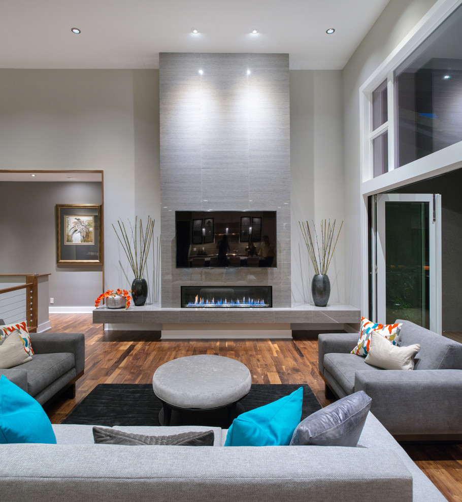 Large trendy medium tone wood floor living room photo in Kansas City with gray walls and a tile fireplace