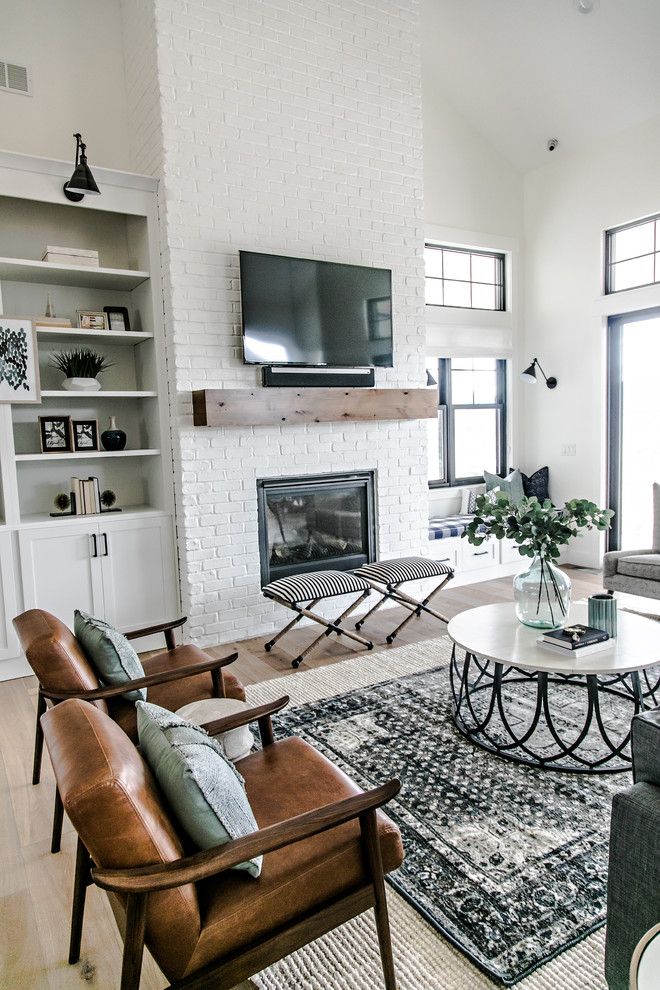 Living room - mid-sized farmhouse formal and open concept medium tone wood floor and brown floor living room idea in Salt Lake City with white walls, a standard fireplace, a brick fireplace and a wall-mounted tv